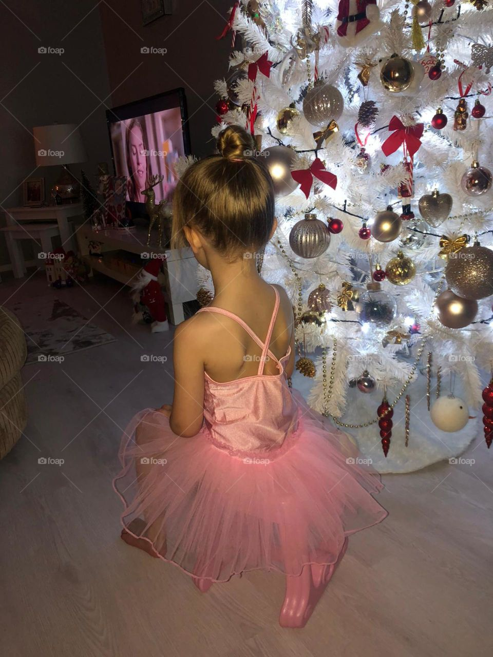 Little princess sitting next to the Christmas tree