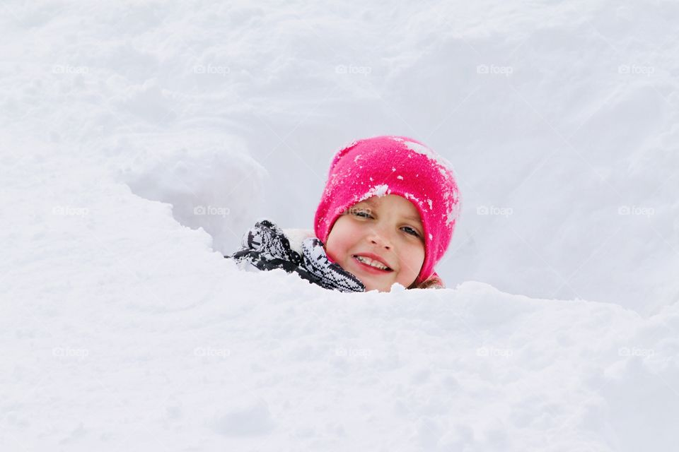 Darling little girl with bright pink stocking hat on sticking her head out of a snow fort is a sure sign of winter!