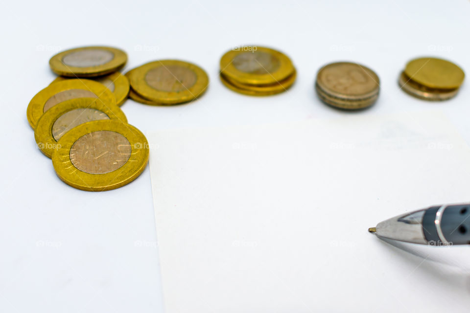 financial planning with coins and a pen isolated on a white background. Selected focus, narrow depth of field. Calculation of financial growth and investment concept