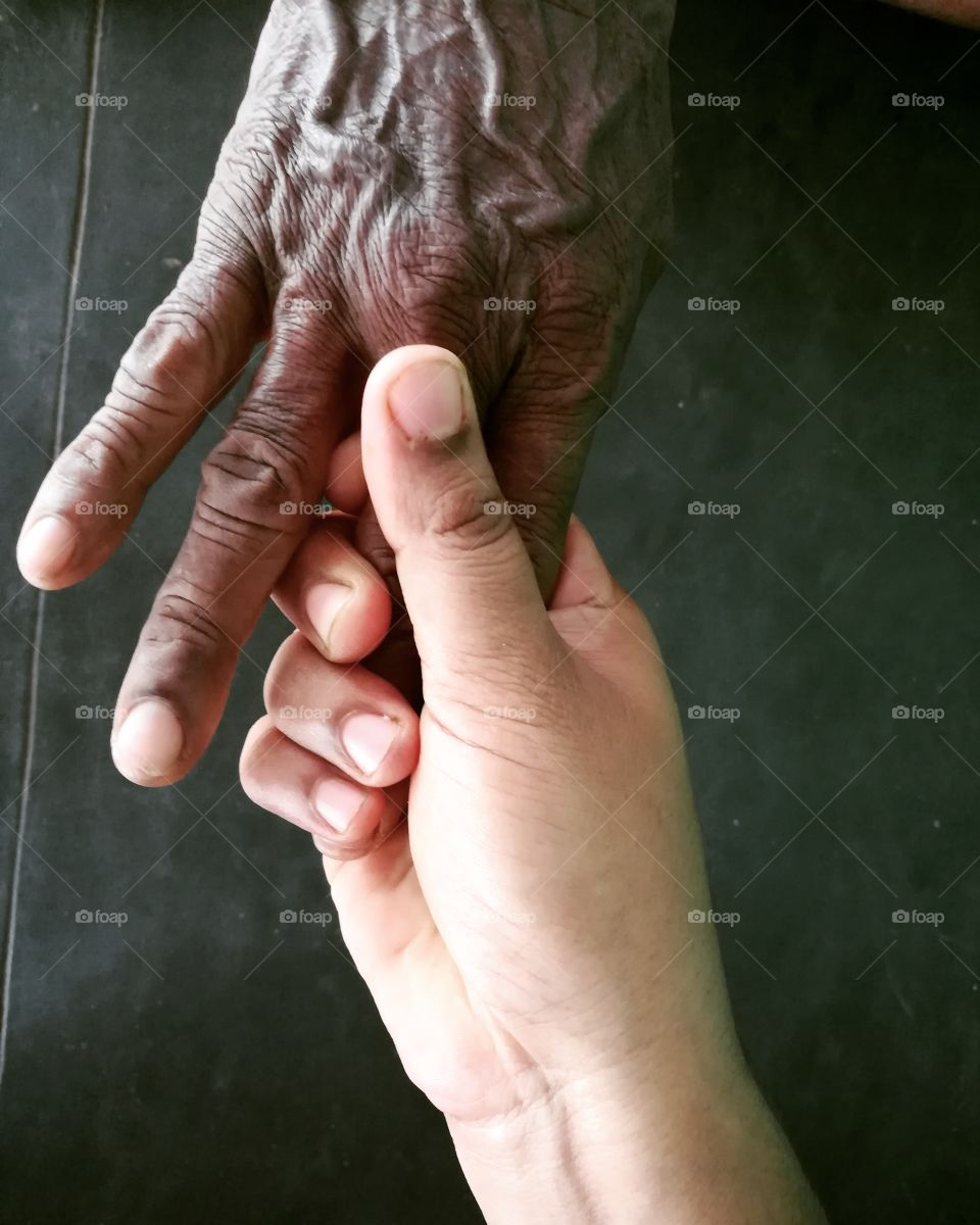 Close-up of grandmother and granddaughter holding hands