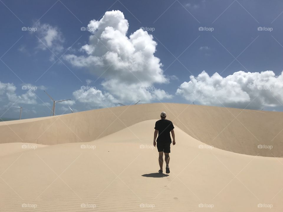 Man walking over sand dunes Ceará Brazil