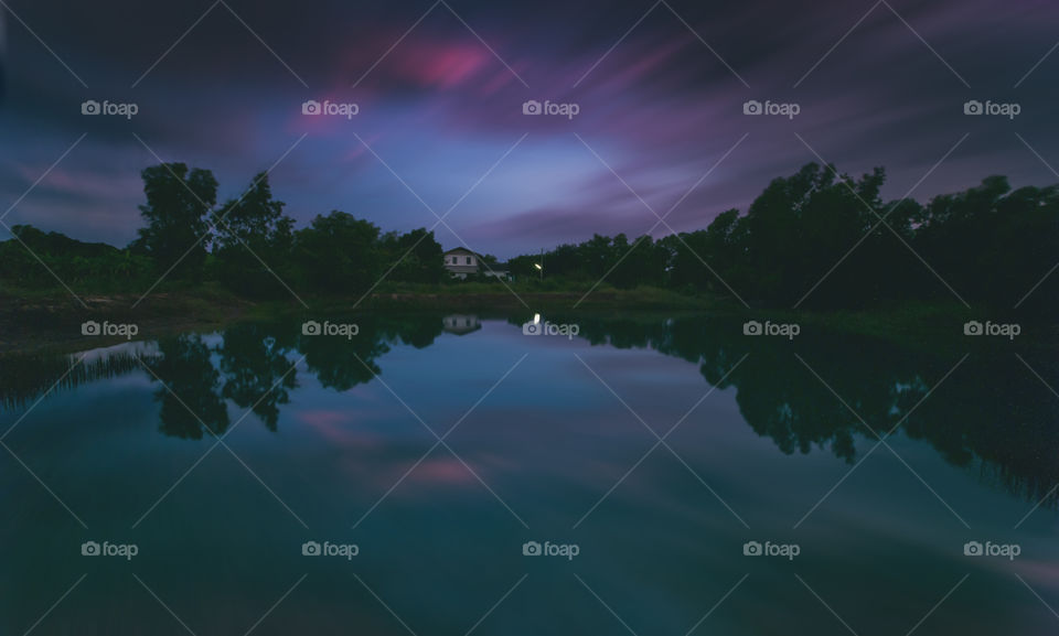 long exposure shot of reflection of nature in a pond during blue hour before sunset.