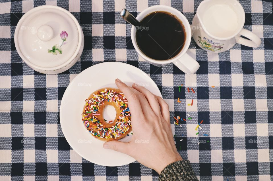 Person's hand with donut and cup of coffee