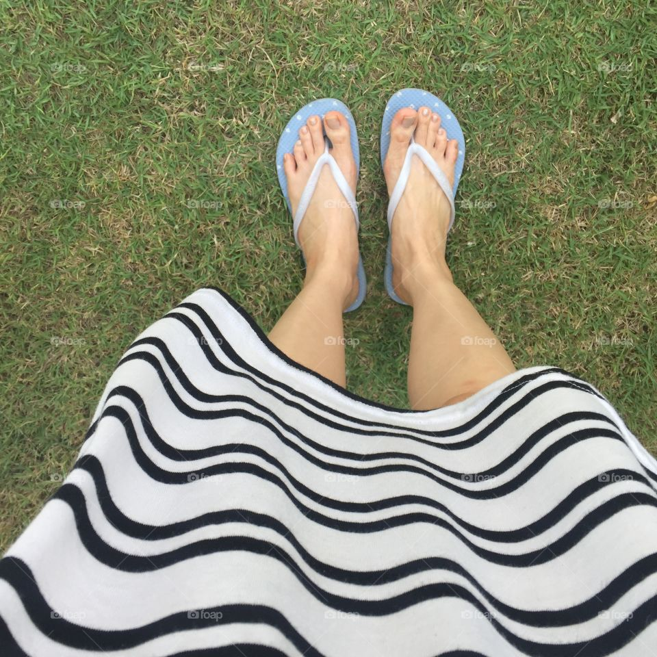 Closeup of bright flip flops and legs on green grass great for any use.