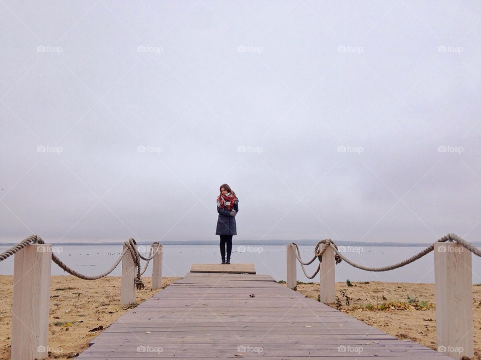 Young woman standing on board walk at beach
