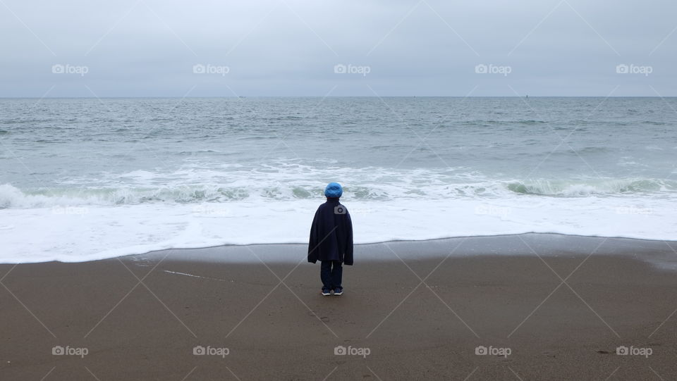 Boy wearing dad's oversized jacket and stares at the incoming waves.