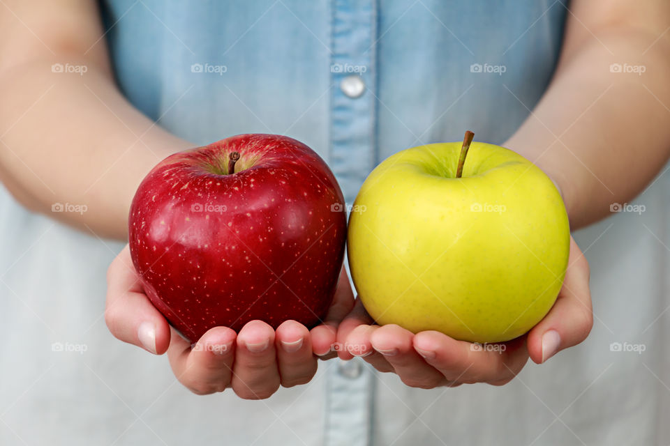 Close-up of person holding red and green apples
