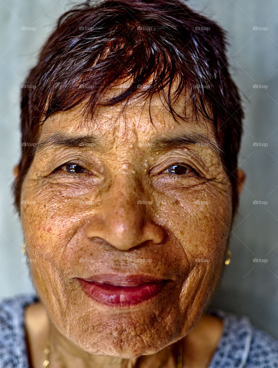 A smiling portrait of an old asian woman