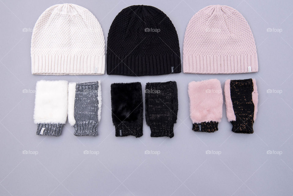 Flat lay of three pairs of beanie hats and fingerless gloves