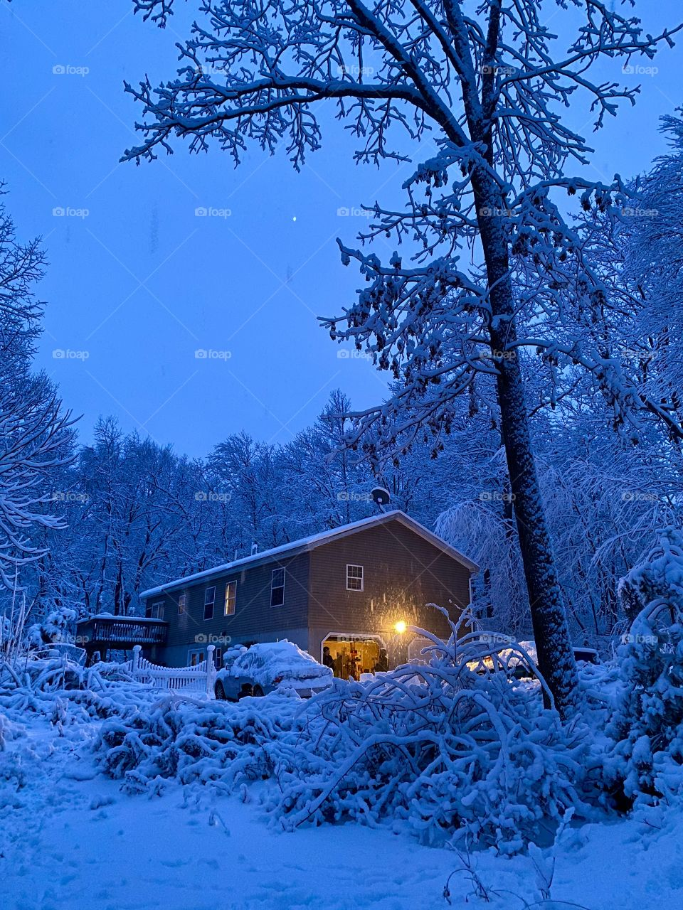 Snow covered scenery and house with garage light on during a heavy snow storm