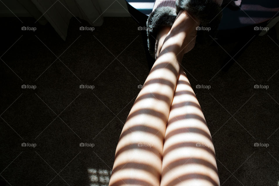 Shadows of window blinds on a woman's legs