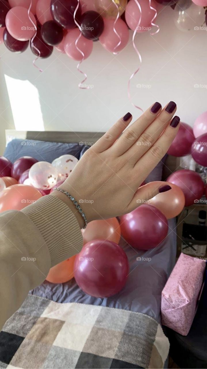 Hand with a bracelet on the background of a room full of balloons