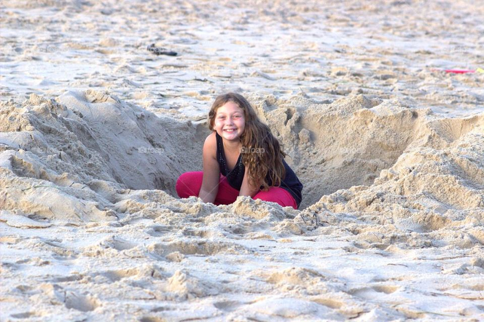 Girl digging in the sand on the beach