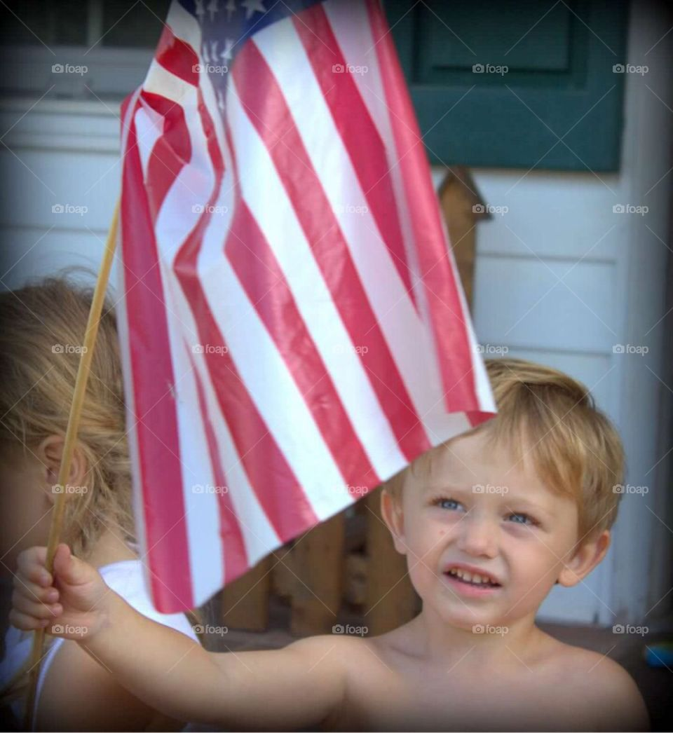 Two year old little boy gazing upwards at the American flag in his hand.
