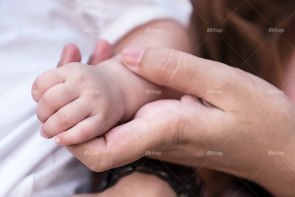 A person holding infant hand