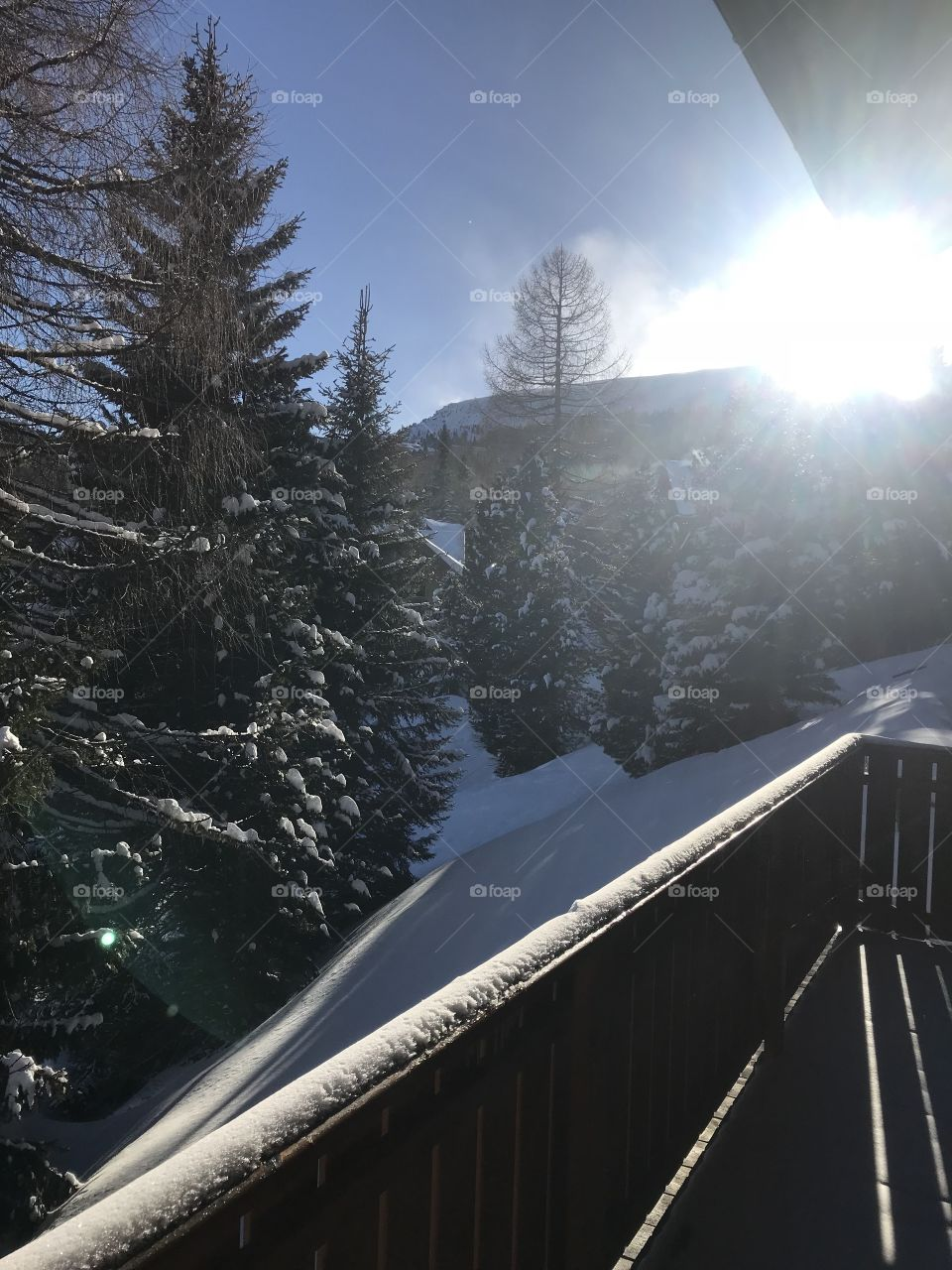 Sun shining in outside of of bungalow in the Austrian Alps. Beautiful fresh powdery snow