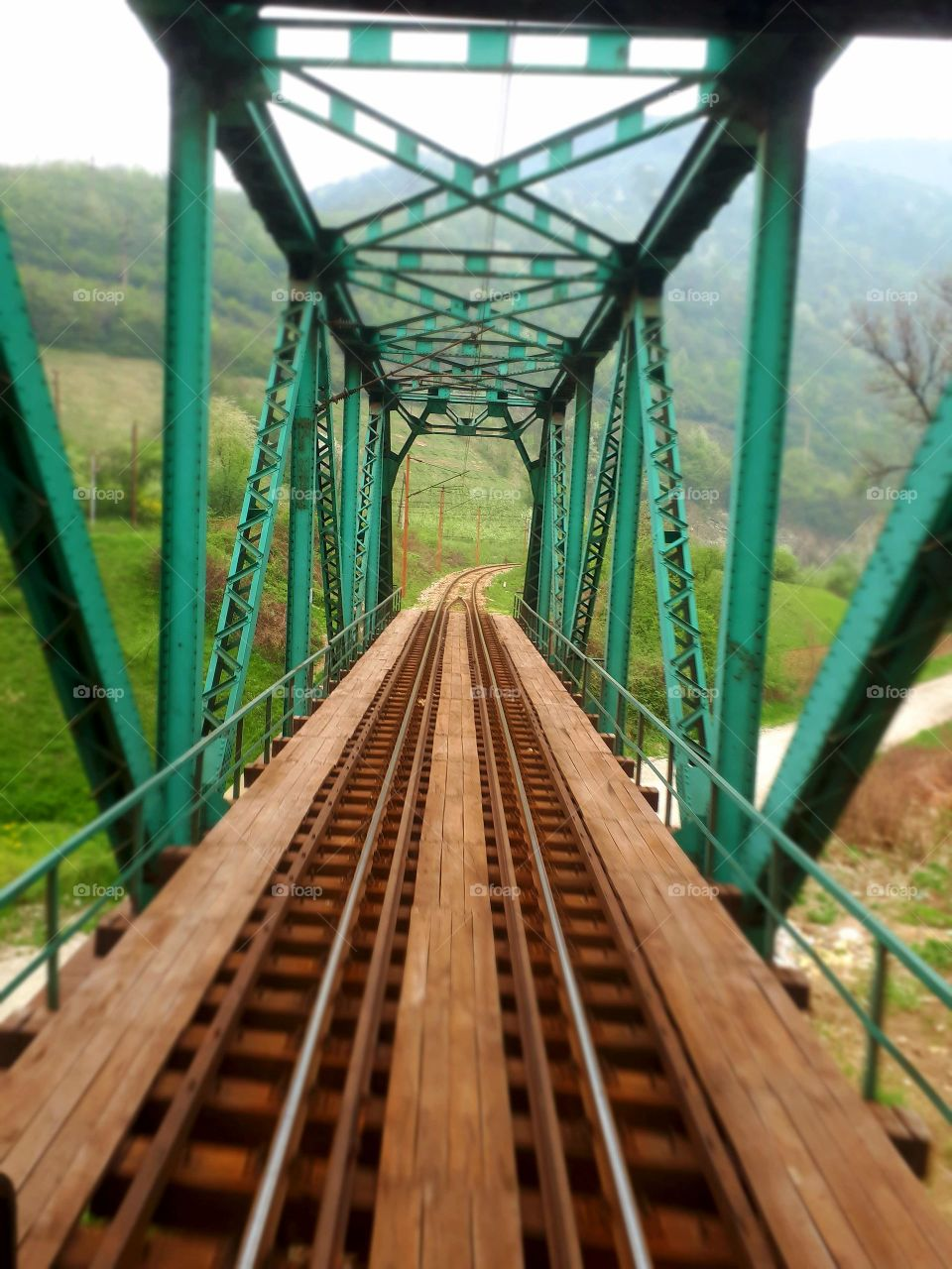 A view from the window of the last passenger wagon to the railway green bridge on the river of Bosna.