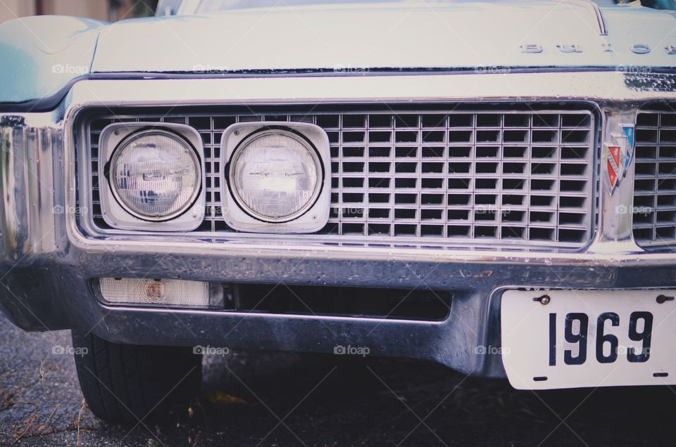 Picture of a vintage car that is almost grey, with the year 1969 shown on the licence plates.