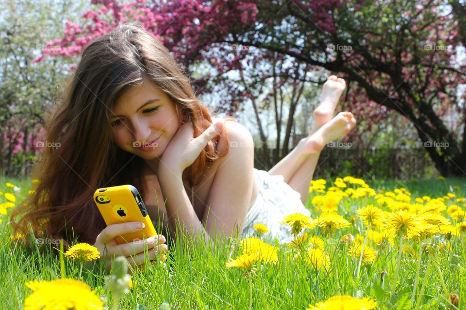 Woman lying on grass with mobile phone