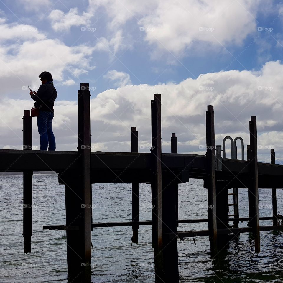 Silhouette figure standing at the pier