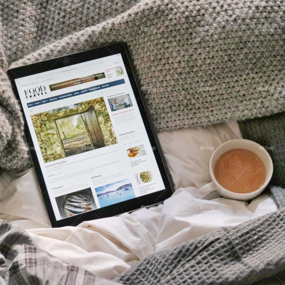 iPad and tea in unmade bed.