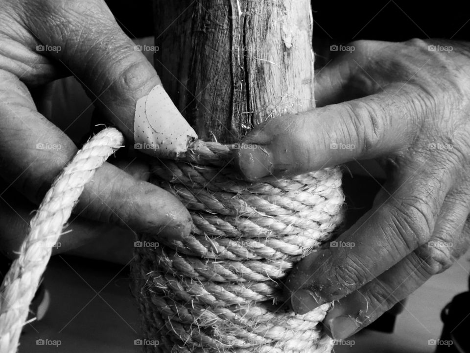 Human hand with rope and wooden pole