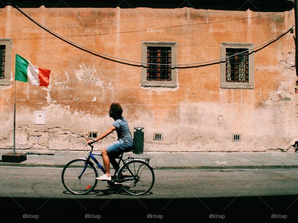Man biking in Pisa, Italy