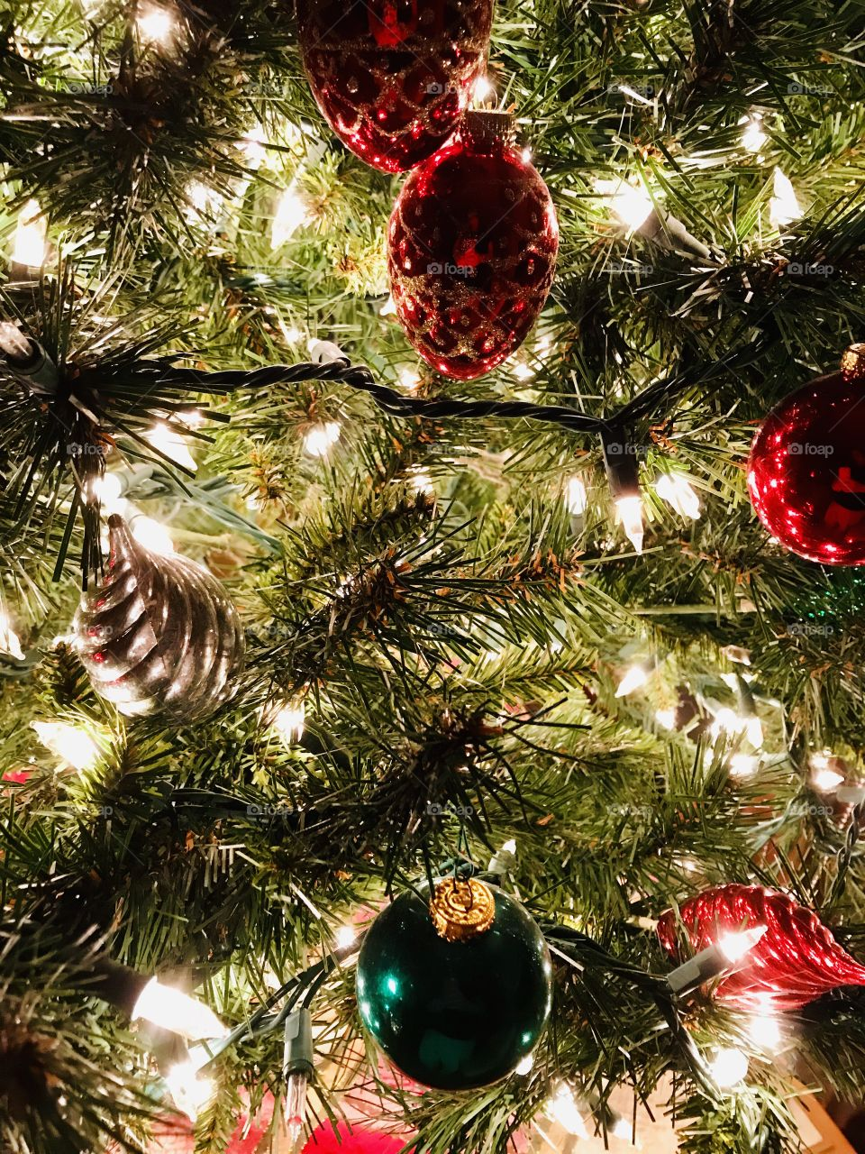 Close up of Christmas tree with white lights and red, gold and green shiny ornaments