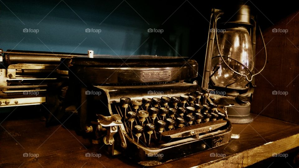 Typewriter with oil lamp on wooden desk