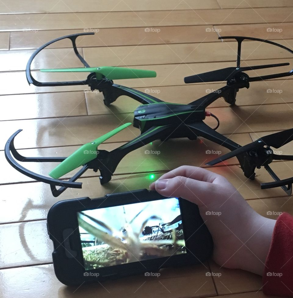 Green and black drone on wood floor. Hand holding iPhone watching drone video footage.