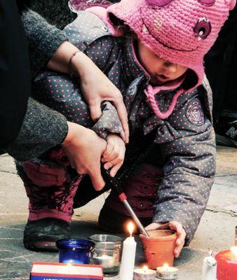 Kid lighting vigil candel