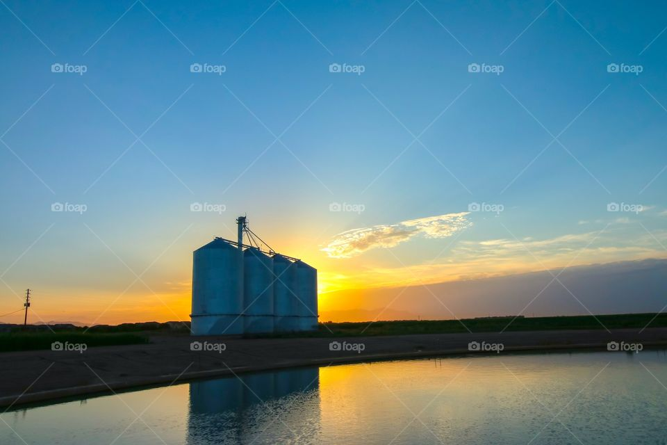 Scenic view of silos at sunset