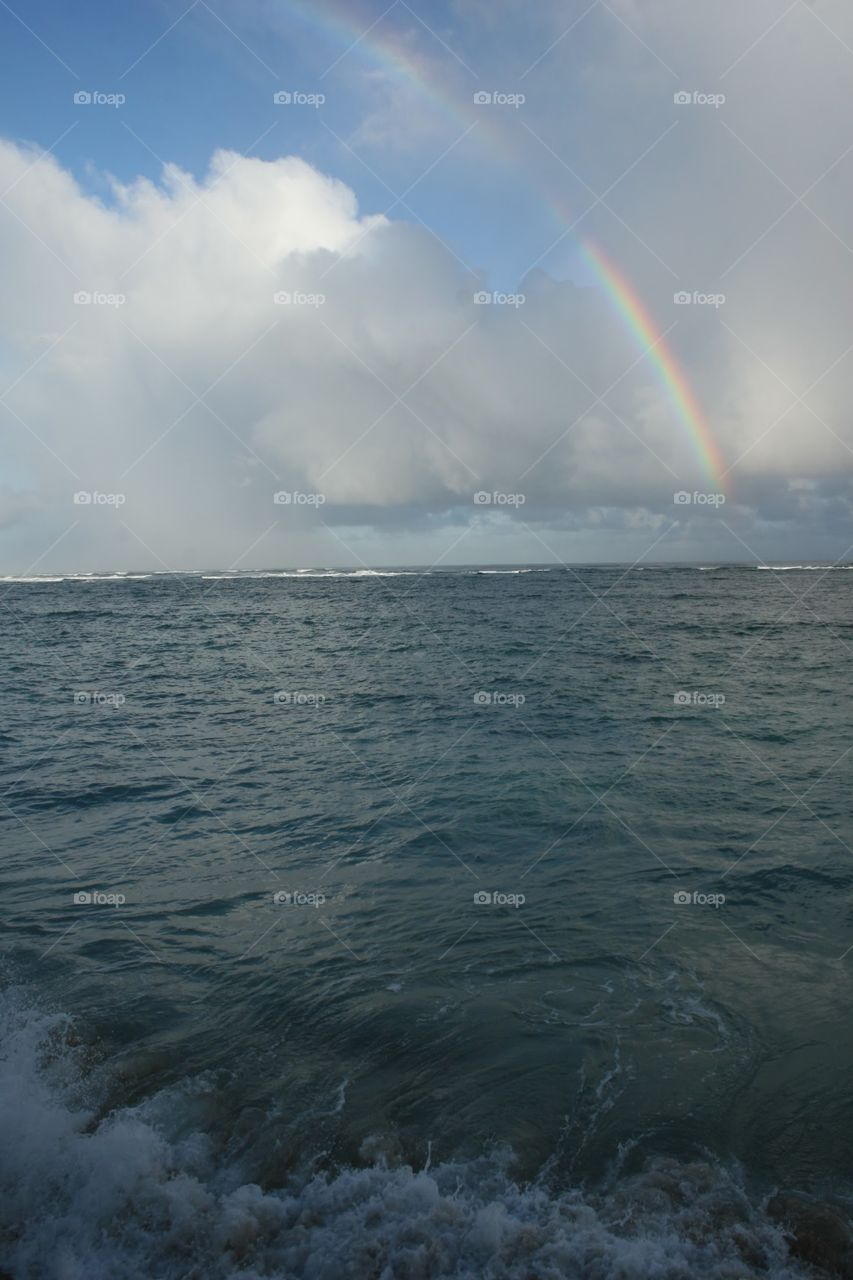 Rainbow, White Clouds & Surf. A rainbow rises over the ocean as waves hit the shore.