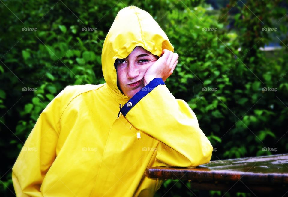What a bad weather. Girl in a yellow raincoat with frustrated  facial expression on a rainy day