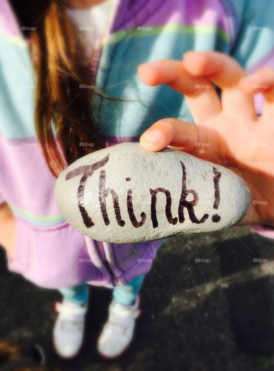 Think! Painted in black ink on a rock held by a girl in the background. You can't see her face.