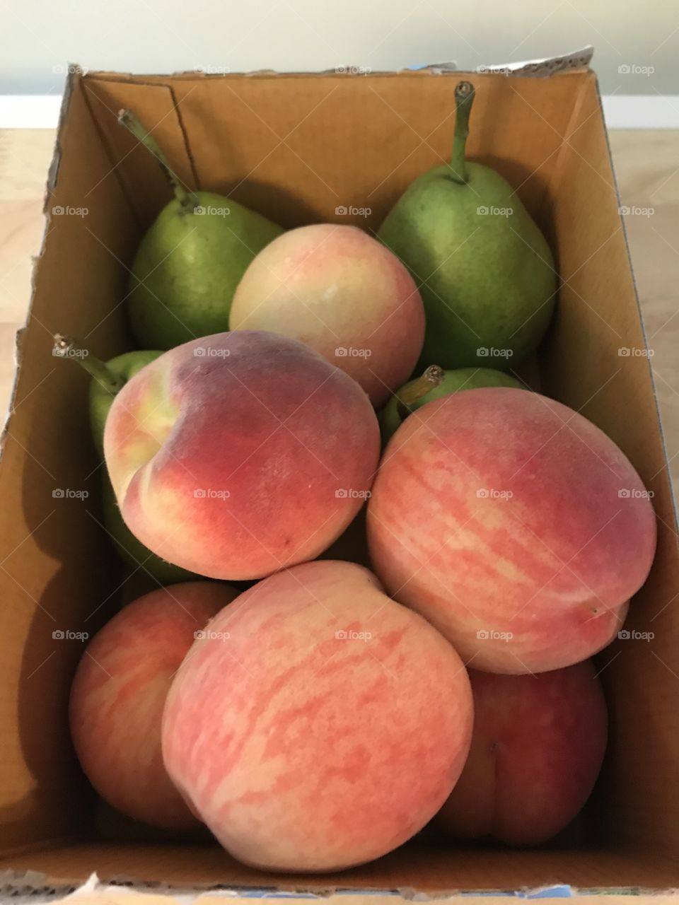 Box of orange peaches and green pears