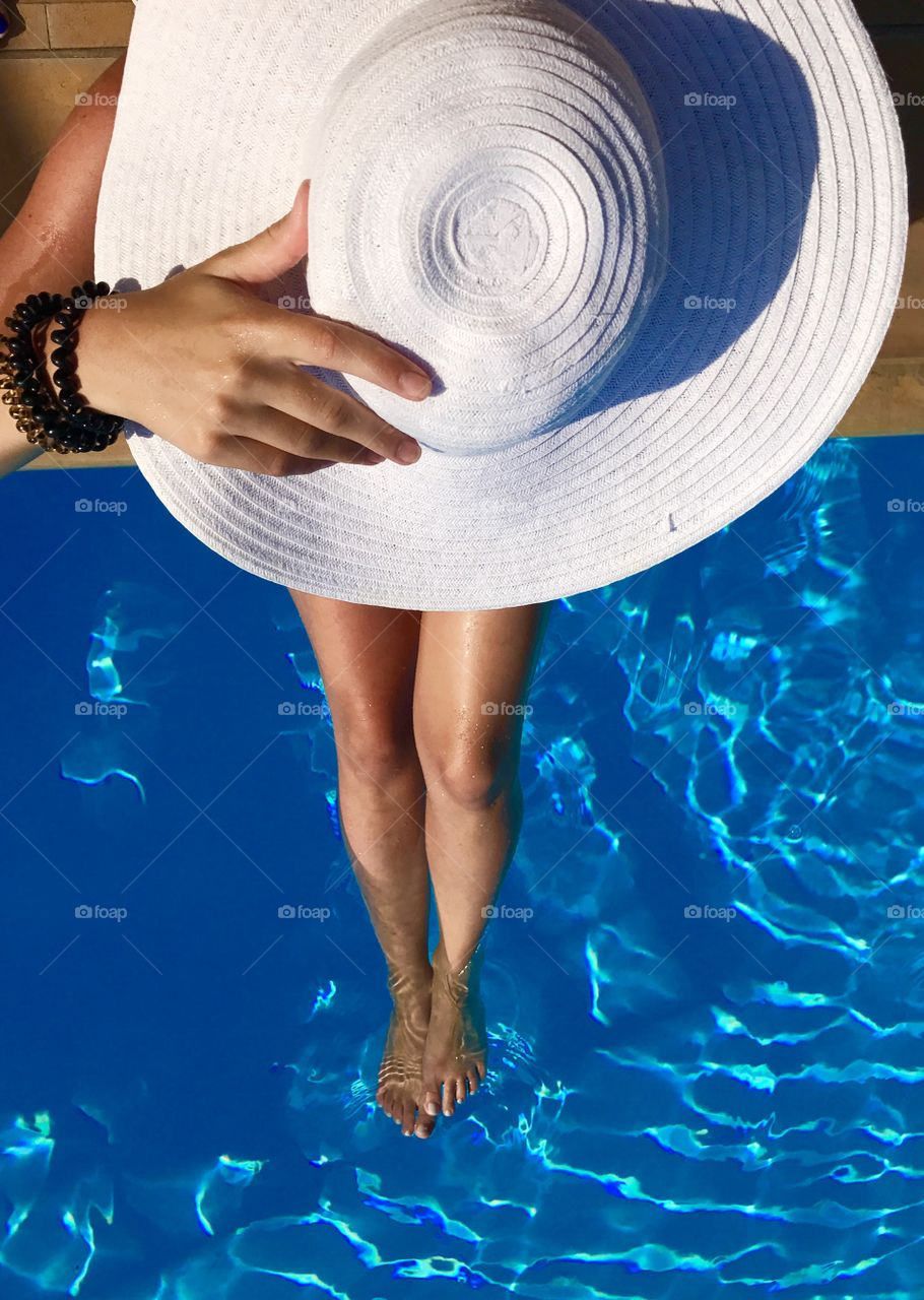 Woman with hat in a pool
