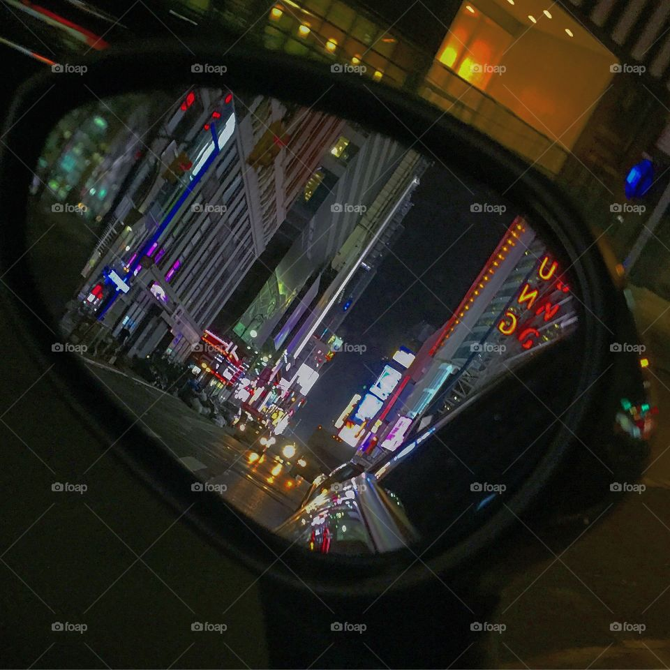 Times Square in rear view mirror.