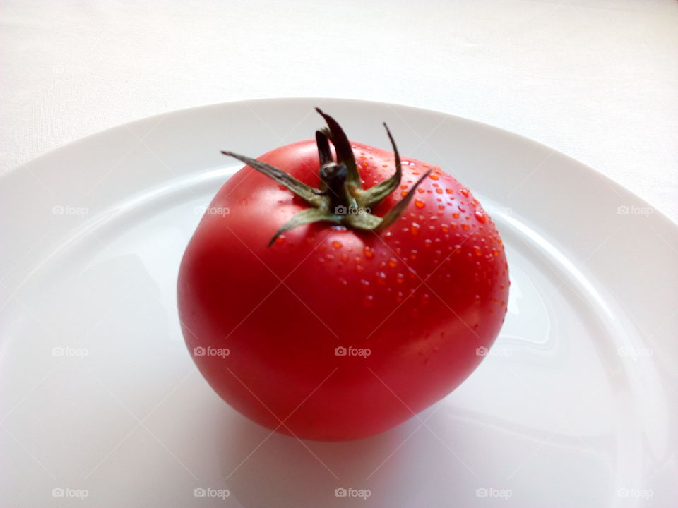fresh red tomato with drops of water on the white plate