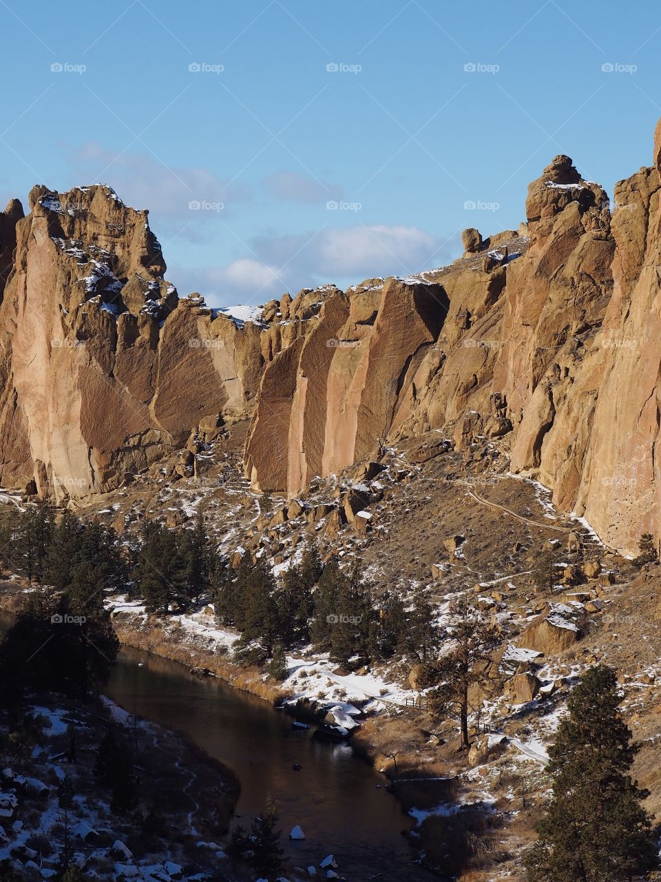 The Crooked River in Central Oregon flows through Smith Rocks State Park with a layer of snow on a sunny winter day.
