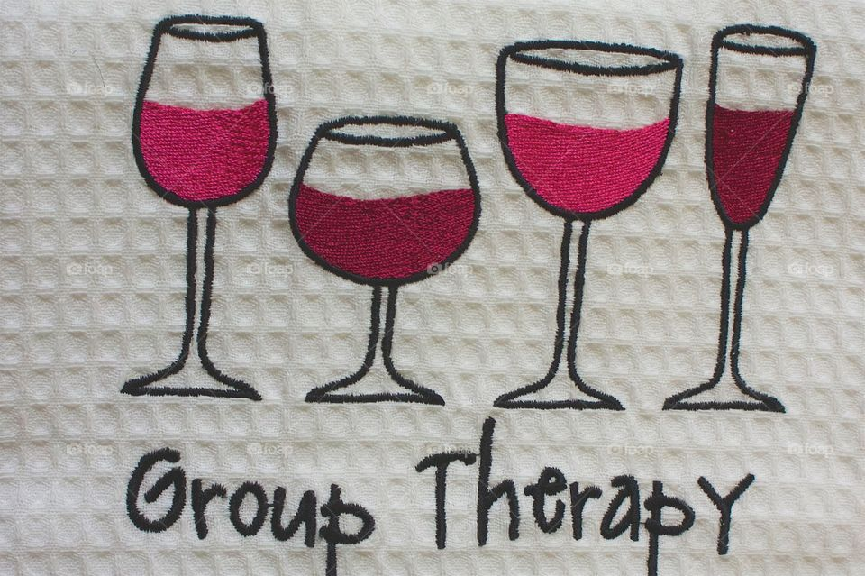 """A dish towel had embroidered wine glasses and the words """"Group Therapy was found in a store in a quaint town (population: 600) Micanopy, Florida."""
