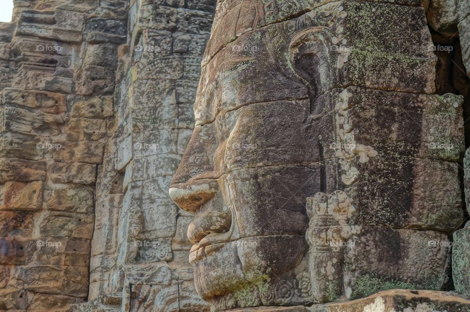 Buddha . Buddhas face carved in stone at complex of temples in Anglor Wat in Cambodia