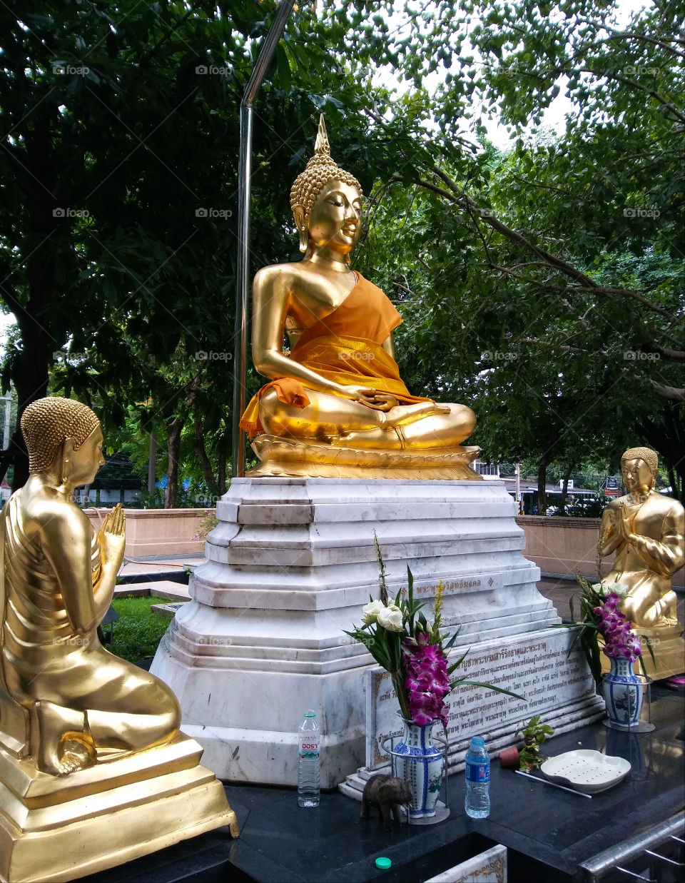 Golden buddha and disciples statue in the park.