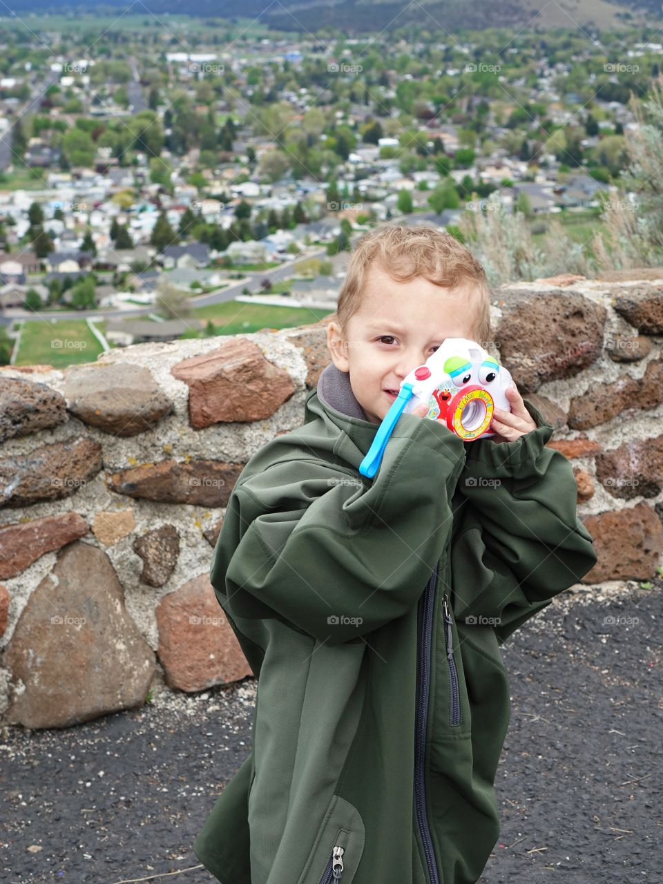 A cute young boy in an adult jacket that hangs to the ground takes a photo with his toy camera.