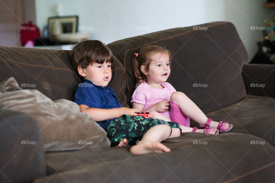 Concentrated toddlers boy and girl playing video game sitting on sofa at home