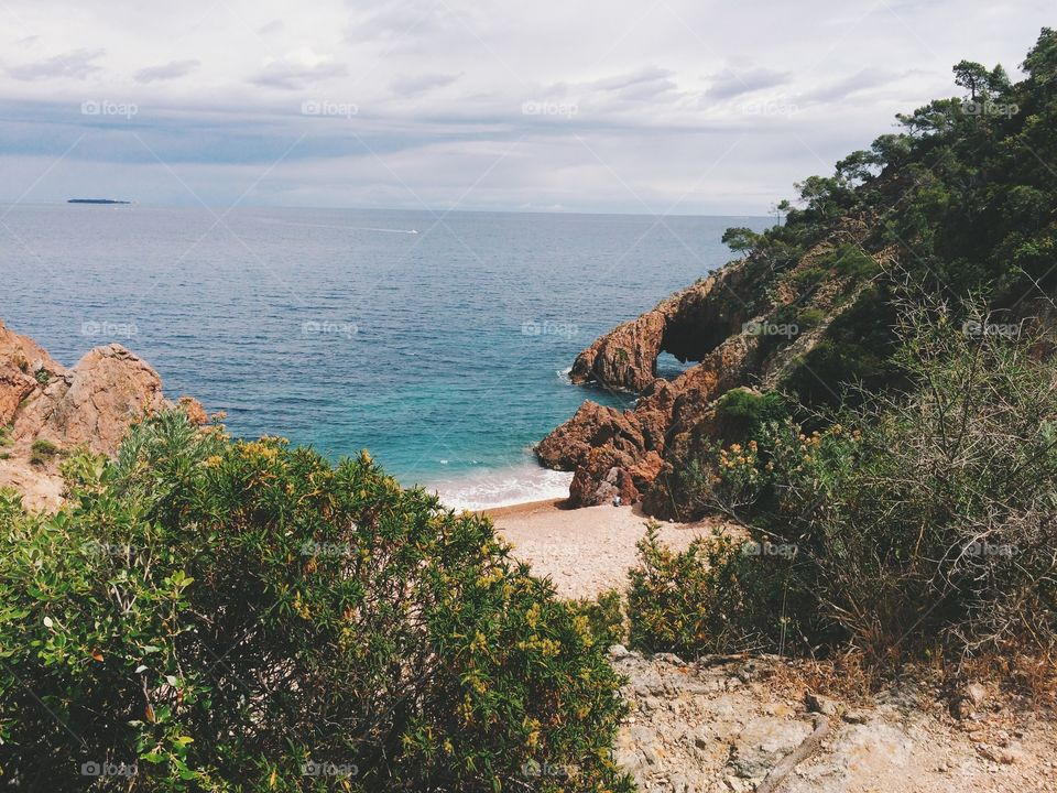 Secluded cliff lined beach in French Riviera. Rocky beach on the Mediterranean Sea in France