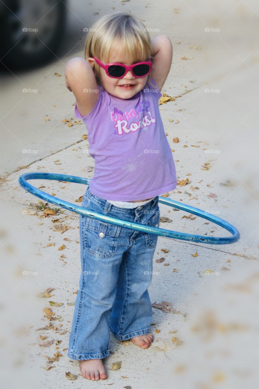 Darling photo of little girl in her shades and Daddy Rocks shirt having fun hula hooping for some good activity!!