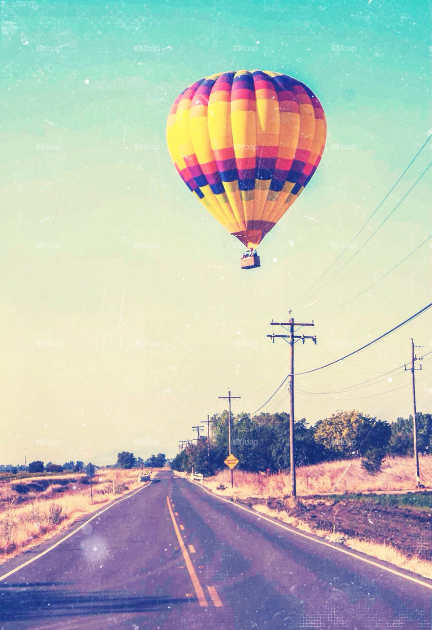 Hot air balloon flying above country road