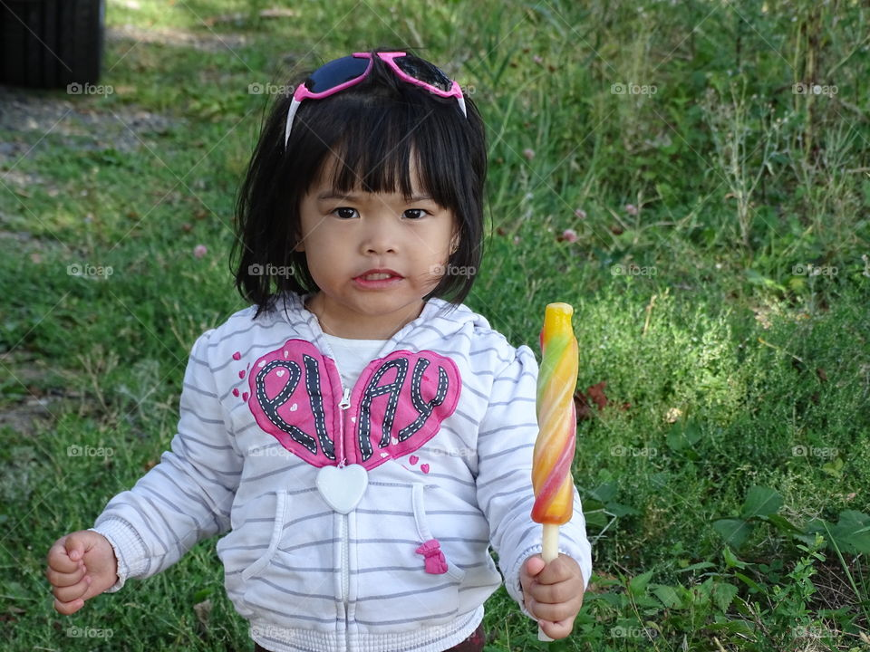 A little girl with popsicle ice standing on grass