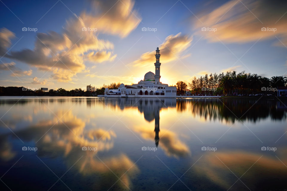 Reflections of mosque during sunset with dramatic sky reflections